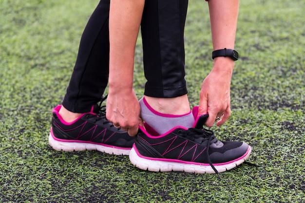 Las manos de la niña llevan zapatos deportivos en el estadio deportivo.