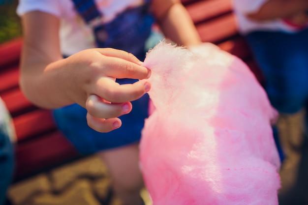 Las manos de niña sosteniendo algodón de azúcar rosa en el fondo de cielo azul