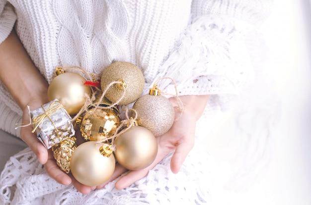 Manos de niña sosteniendo bolas de navidad doradas y plateadas