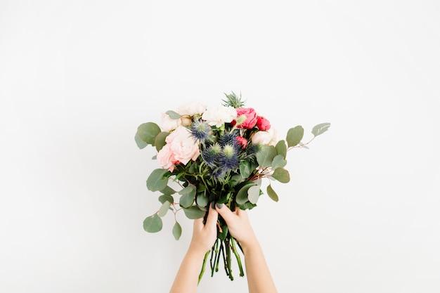 Manos de la niña sosteniendo un ramo de flores hermosas: rosas grandilocuentes, eringio azul, eucalipto, aislado en blanco