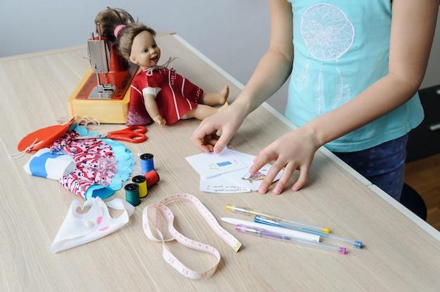 Las manos de la niña sostienen los bocetos de la ropa para la muñeca. en el escritorio hay bolígrafos, lápices, cinta métrica, tela, máquina de coser y muñeca.