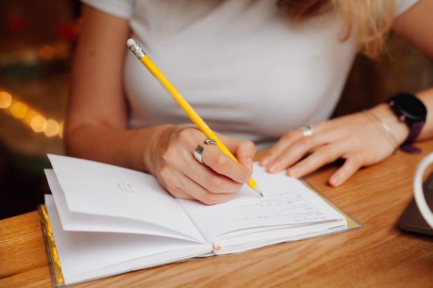 Las manos de las niñas escriben con lápiz amarillo en una página blanca del bloc de notas