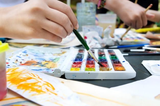 Manos de niñas sumergiendo pinceles en la pintura de cerca durante la lección de dibujo