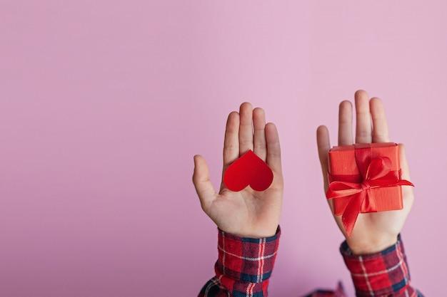 Manos del niño con corazón de papel rojo y caja presente en la mano. concepto de día de san valentín