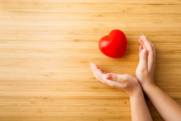 Manos de niño con corazón rojo, cuidado de la salud, concepto de donación y seguro familiar