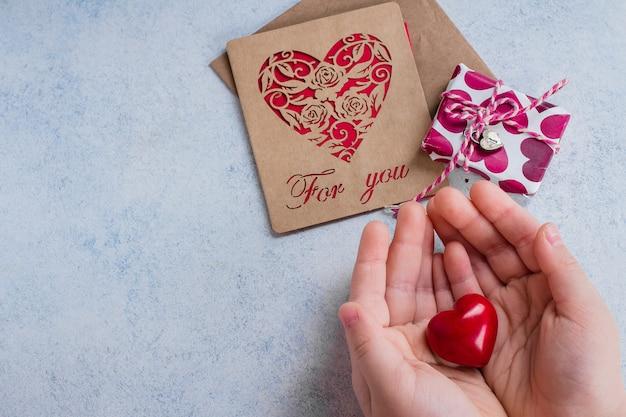 Manos del niño con corazón rojo