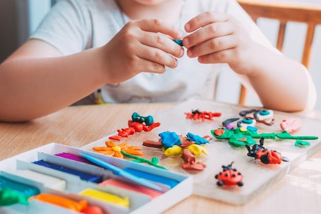 Las manos del niño esculpen figuras de plastilina suave clases educativas y entretenidas con niños primer plano
