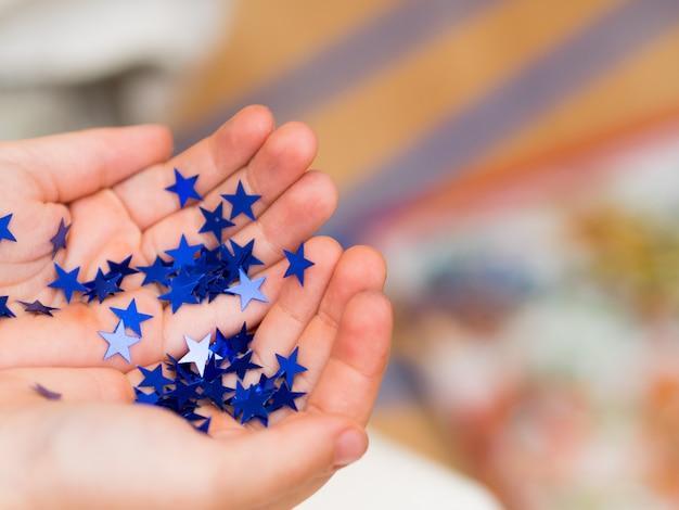 Manos del niño con estrellas brillantes. concepto de vacaciones de navidad copia espacio