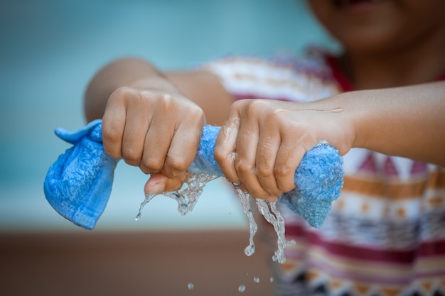 Las manos del niño exprimen la toalla azul mojada