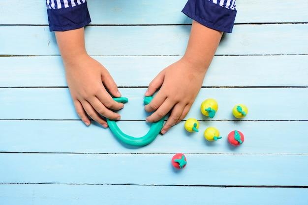 Las manos del niño jugando a clay y usando la creatividad para hacer líneas y frutas