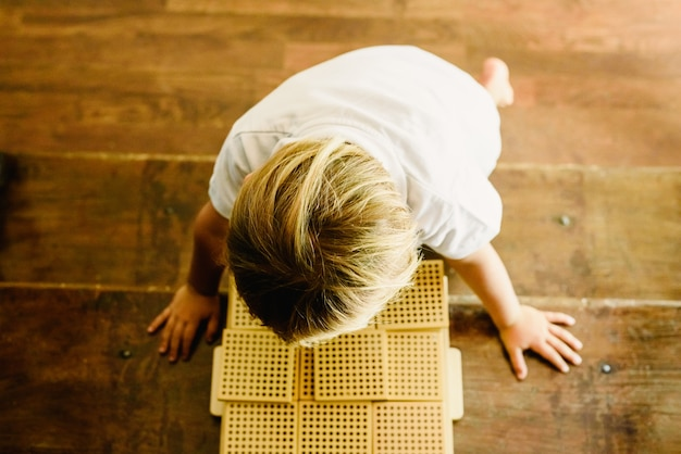 Manos de niño manipulando contando cubos sobre fondo de madera en el aula de montessori
