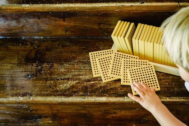 Manos del niño manipulando el conteo de cubos sobre fondo de madera en el aula montessori