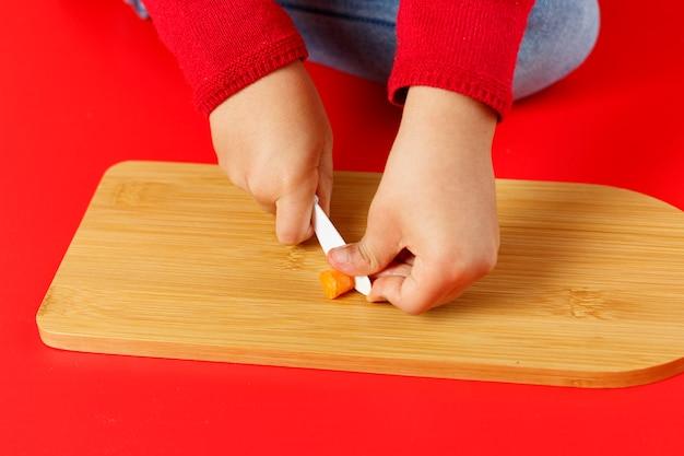 Manos de niño pequeño cortando zanahorias en la mesa