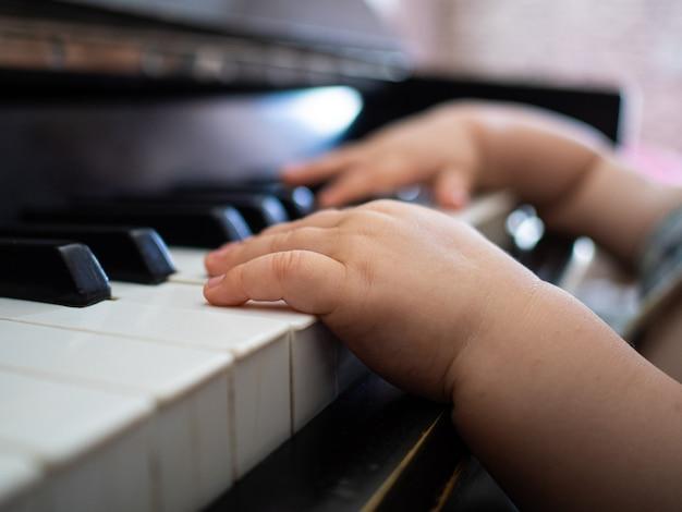 Manos de un niño pequeño tocando las teclas del piano