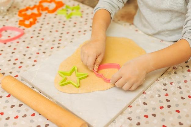 Manos del niño preescolar haciendo galletas con moldes para galletas