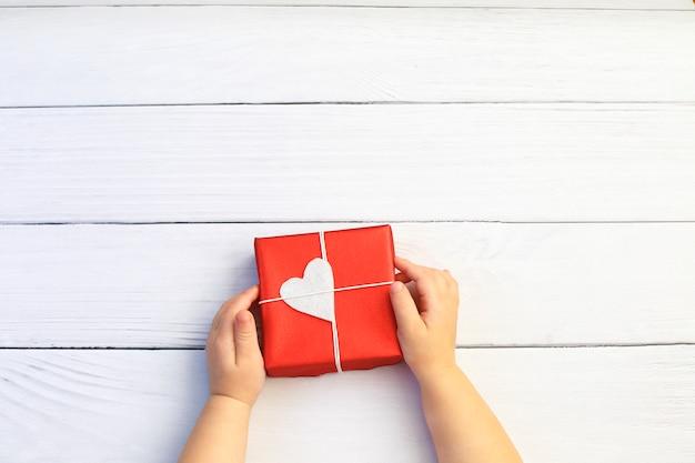 Manos del niño que sostienen la caja de regalo hermosa en el fondo de madera