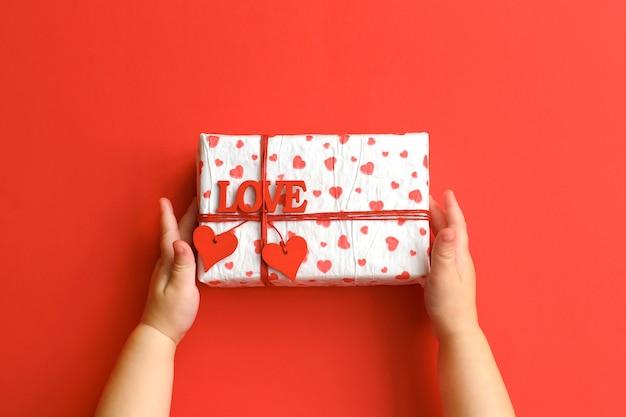 Manos del niño que sostienen la caja de regalo hermosa en fondo rojo