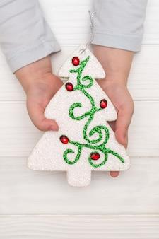 Manos del niño sosteniendo el árbol de navidad ornamental en mesa blanca