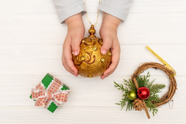 Manos del niño sosteniendo la bola de navidad cerca de cajas de regalo en blanco