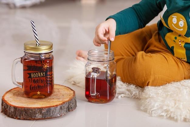 Las manos del niño sosteniendo una taza de té. tiempo de fiesta. tarro de té con bebida