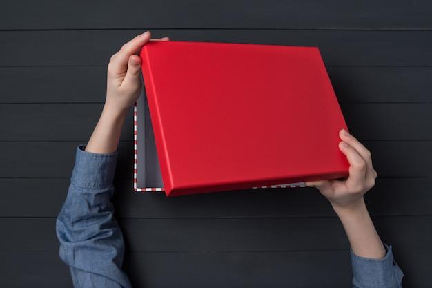 Las manos de los niños abren una caja de regalo con tapa roja. vista superior