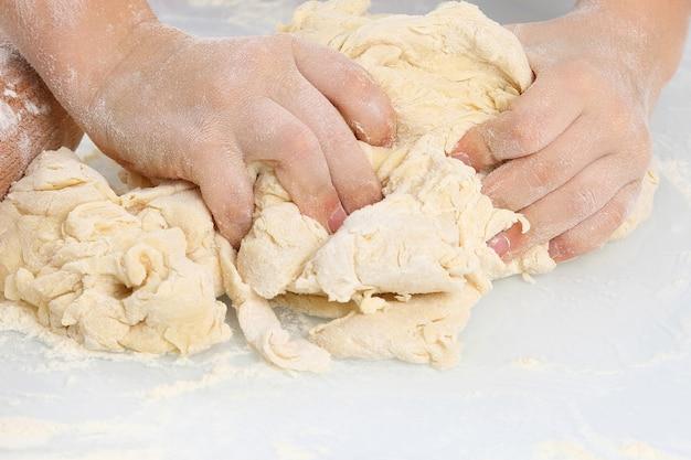Las manos de los niños amasan la masa sobre un fondo claro. cocinar y hornear pizza