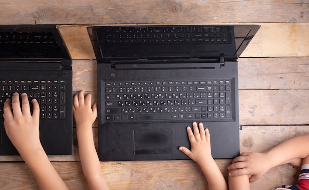 Manos de niños aprendiendo cursos en línea, vista superior
