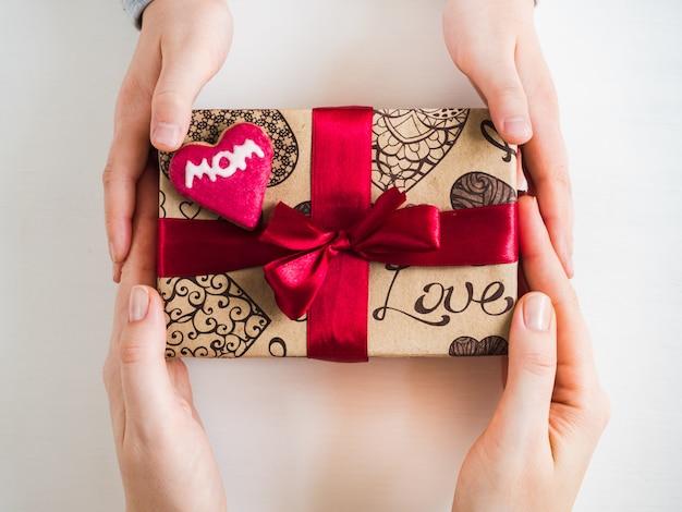 Las manos de los niños y una caja con un regalo.