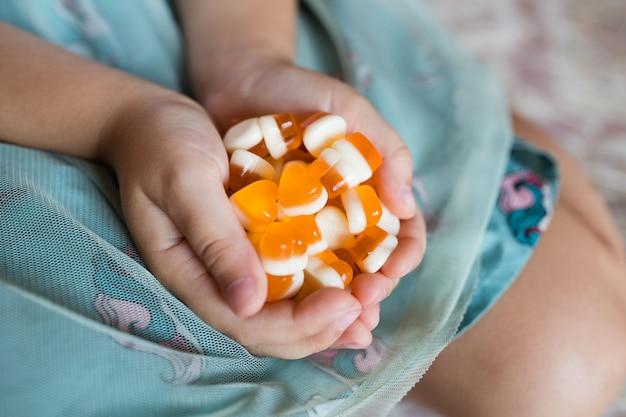 Manos de niños con caramelos de naranja