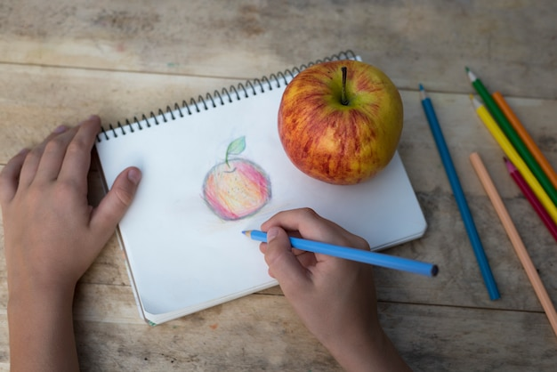 Las manos de los niños dibujan una manzana con lápices de colores. vista superior