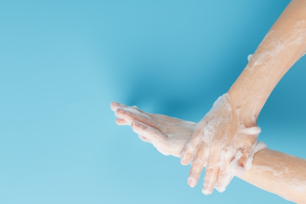 Las manos de los niños en espuma de jabón sobre un fondo azul close-up