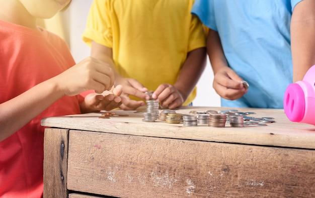 Las manos de los niños están ayudando a poner monedas en la hucha en blanco