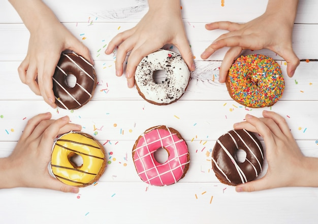 Las manos de los niños están quitando los coloridos donuts.