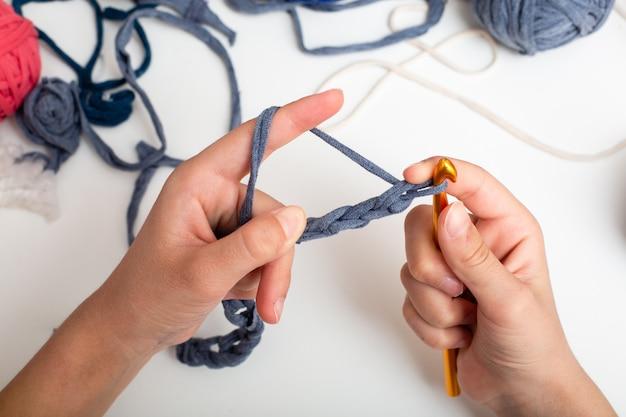 Las manos de los niños están tejidas a ganchillo e hilo. vista desde arriba
