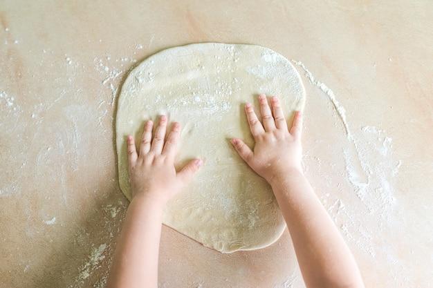 Las manos de los niños hacen masa