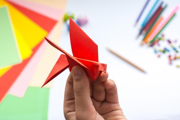 Las manos de los niños hacen origami ave de papel rojo.