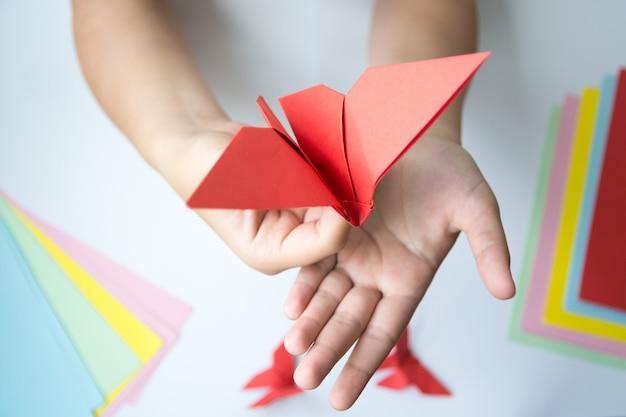 Las manos de los niños hacen origami mariposa de papel rojo.