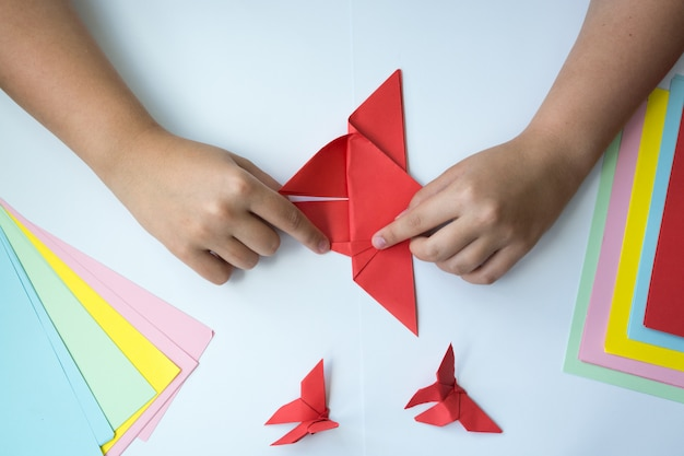 Las manos de los niños hacen origami una mariposa.