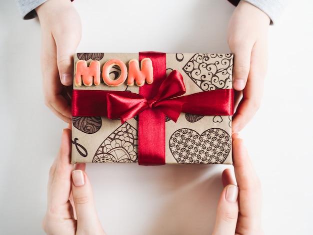 Manos de niños, hermosa caja con un regalo.