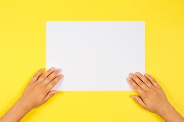 Manos de los niños con hoja de papel en blanco blanco sobre fondo amarillo