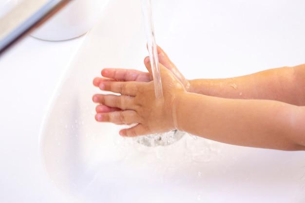 Las manos de los niños se lavan. manos de niños en espuma de jabón antibacteriano. protección contra bacterias, coronavirus. higiene de manos. lavado de manos con agua