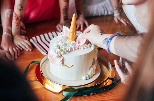 Las manos de los niños las niñas alcanzan el pastel. gran unicornio hermoso pastel en el cumpleaños de la pequeña princesa en la mesa festiva