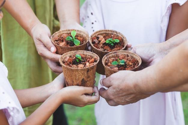 Manos de niños y padres sosteniendo juntos plántulas jóvenes en macetas de fibra reciclada