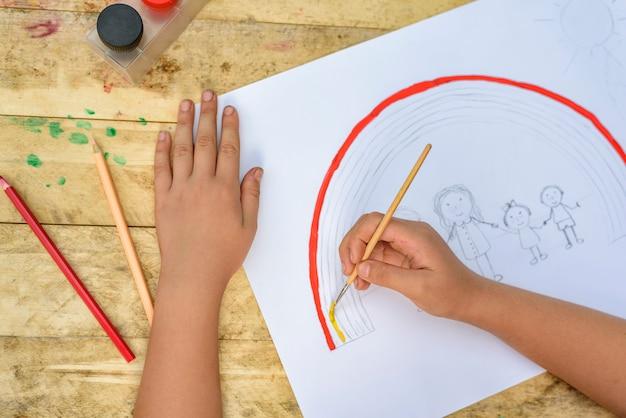 Las manos de los niños pintan un dibujo con pincel y pinturas. vista superior