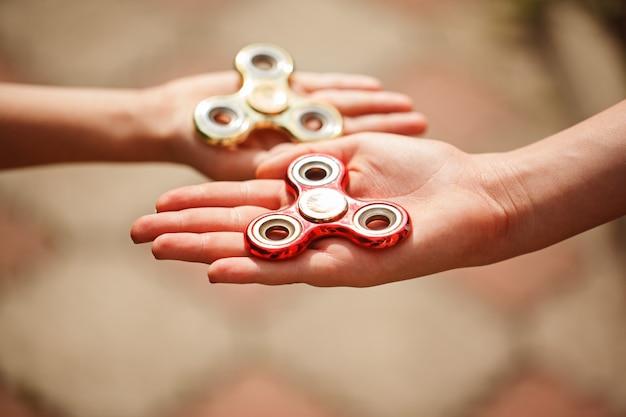 Manos de los niños que sostienen hilanderos de mano fidgqet. juguete de moda y popular para niños y adultos.
