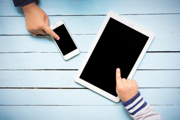 Las manos de los niños que usan la tableta en la tabla azul de madera.