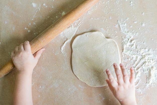 Las manos de los niños rodaron la masa