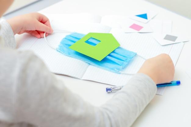 Manos de los niños sosteniendo una máscara protectora médica con casa verde de papel sobre el cuaderno escolar en el escritorio en casa. concepto de estudio de cuarentena.