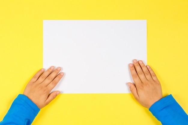 Manos de los niños con tarjeta de papel en blanco blanco sobre fondo amarillo