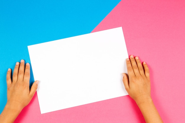 Manos de niños con tarjeta de papel en blanco blanco sobre fondo azul y rosa